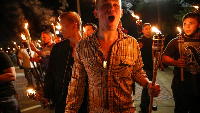 White nationalist groups march with torches through the UVA campus in Charlottesville.