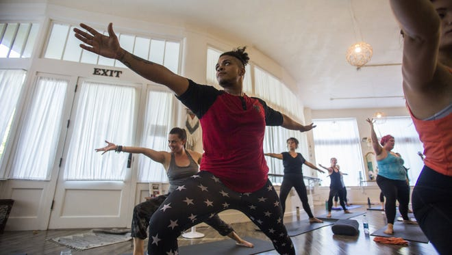 Shuja DePeace, center, a friend of Abiola Akanni and instructor for Yoga N Da Hood - a donation-based yoga program focusing on classes in poorer neighborhoods - strikes a warrior pose as part of the Trap Vinyasa routine at Bohemian Studios. (Kjell Redal/The Seattle Times/TNS)