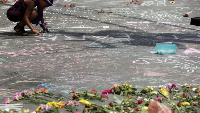 A woman leaves a message in chalk on the street where Heather Heyer was killed.