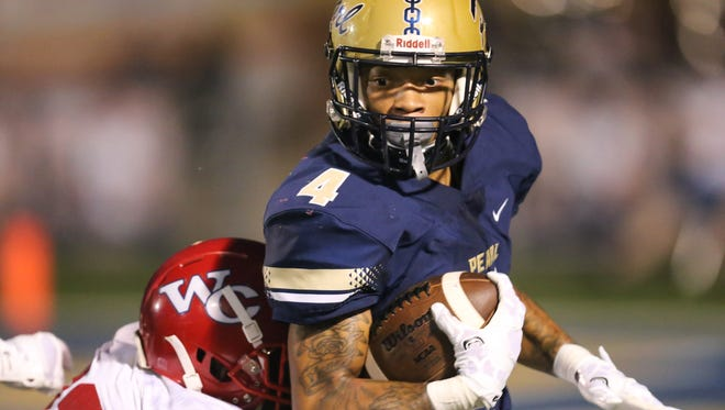 Pearl's Johnquarise Patterson is hit by Warren Central's David King after making a catch in the second quarter of their Friday night game in Pearl.