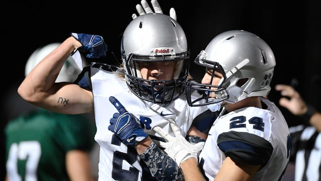 Reitz's Andrew Word (24) congratulates teammate Isaiah Dunham (22) after a touchdown as Evansville Reitz plays Owensboro Catholic in the second game of a double header at the Independence Bank Border Bowl played at Steele Stadium in Owensboro, August 25, 2017.