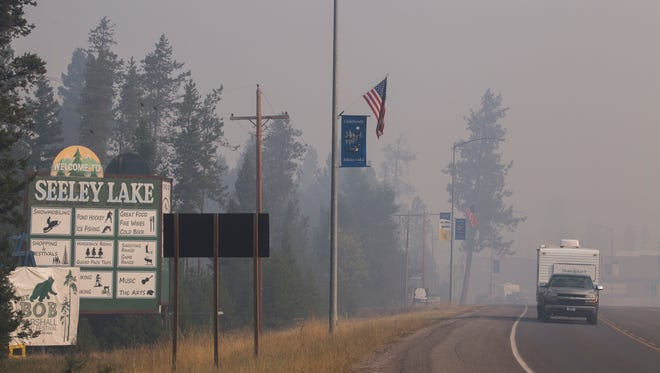 A pickup truck pulls a camper through the wildfire smoke in Seeley Lake on Aug. 10. Gov. Steve Bullock issued an executive order on Friday declaring a state of disaster exists in Montana due to wildfires.