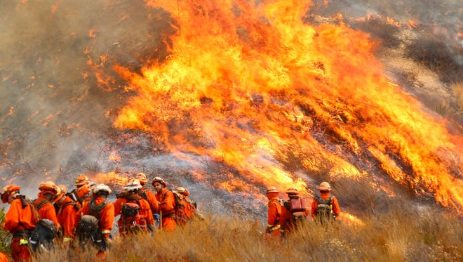 A crew with California Department of Forestry and Fire Protection the La Tuna Fire on a hillside in Los Angeles County on Saturday. Several hundred firefighters worked to contain the  blaze that chewed through brush-covered mountains, prompting evacuation orders.