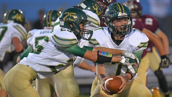 Laconia quarterback Cormac Madigan (7) hands off to Jaylen Mahone (23). The Omro Foxes hosted the Laconia Spartans Friday evening, September 1, 2017 at Drobnick Field.