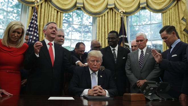 President Trump, Vice President Mike Pence and faith leaders say a prayer during the signing of a proclamation in the Oval Office of the White House Sept. 1, 2017, in Washington, D.C. President Trump signed a proclamation to declare this Sunday as a National Day of Prayer for people affected by Hurricane Harvey.