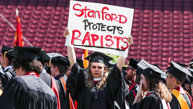 A woman protests during graduation at Stanford University, in Palo Alto, Calif., on June 12, 2016.