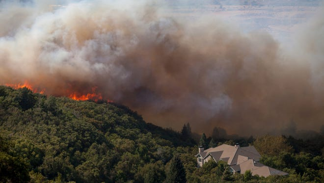 In this Tuesday, Sept. 5, 2017, photo, a wildfire burns through residential areas near the mouth of Weber Canyon near Ogden, Utah. (Benjamin Zack/Standard-Examiner via AP)