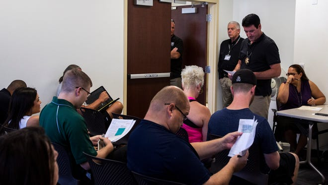 Bidders are pictured at the end of an HOA foreclosure auction at the Maricopa County Sheriff's Office building on Aug. 10, 2017, in Phoenix.