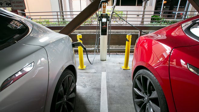 Two Tesla EVs charge at the City of Palo Alto EV charging station in the public garage at 532 Webster St. in Palo Alto,