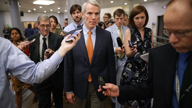 Sen. Rob Portman (R-OH) (C) is pursued by reporters following a vote at the U.S. Capitol on July 31, 2017.