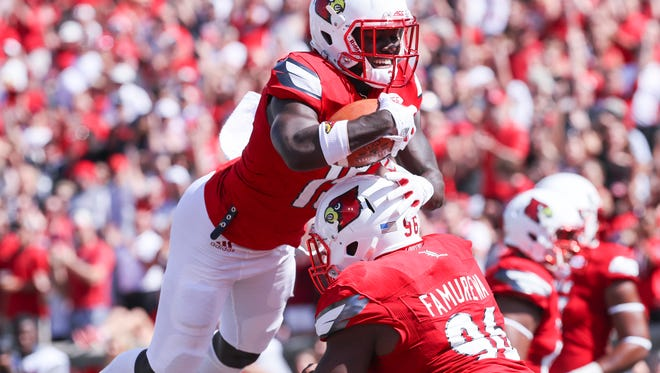Louisville's Trumaine Washington and henry Famurewa celebrate after Washington scored after an interception in the first quarter against Kent State.September 23, 2017