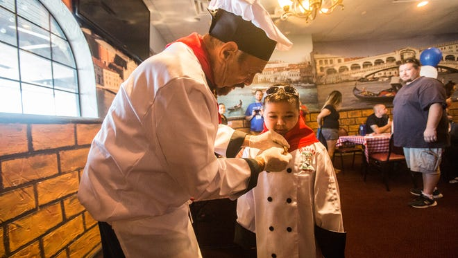 "Mario Del Guidize, owner of Mario's Italian Cafe helps Cohen Powell pot on a chef's outfit. The pair met during a ""Make A Wish Foundation"" event and have become close to one another."