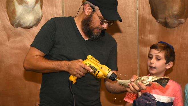 Rabbi Aron Rabin drills the mouthpiece of a shofar. Chabad of Naples opened a shofar factory at their center on Wednesday evening, giving children the chance to turn animal horns into the shofar, used in Jewish observances.