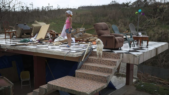 Irma Maldanado stands with her parrot and her dog in what is left of her home that was damaged by Hurricane Maria on Wednesday, Sept. 27, 2017, in Corozal, Puerto Rico.