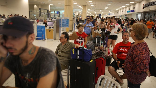 People pass the time waiting in line at Luis Muñoz Marín International Airport in San Juan on Monday hoping to get a flight out of hurricane-ravaged Puerto Rico.