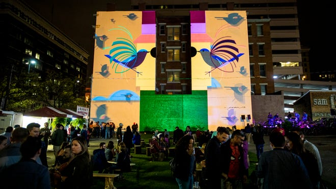 """Our Own Homecoming"" from Cincinnati's We Have Become Vikings honors local artist Charley Harper. The video projection activates an ArtWorks mural of a Harper creation at 119 E. Court St."