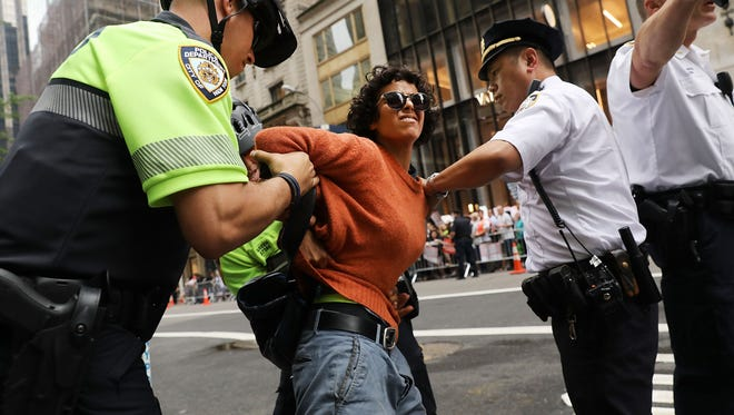 A woman is arrested during a pro-immigration rally outside of Trump Tower along Fifth Avenue on August 15, 2017, in New York City.