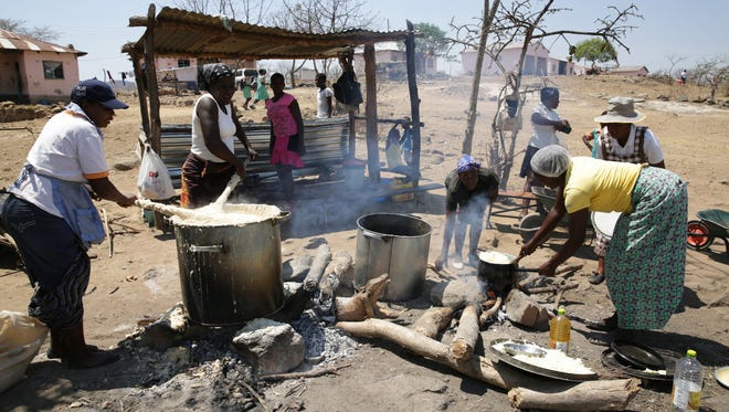 Parents prepare food for their children to eat at lunch time at Munyawiri School just outside Harare, Zimbabwe, on Oct. 16, 2017. Zimbabwe joined the international community in celebrating World Food Day which was set aside by the United Nations to stress the importance of fighting hunger globally.