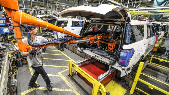 A worker at the Kentucky Truck Plant installs rear seats in the back of a vehicle as redesigned Ford Expeditions and Lincoln Navigators are rolling off the assembly line on Oct. 27, 2017.