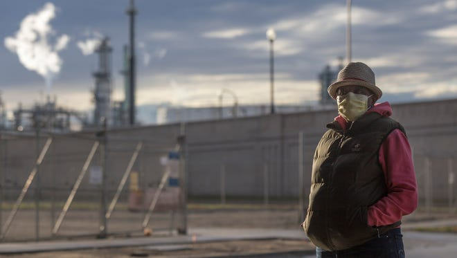Emma Lockridge uses a medical mask to protect herself from pollutants in the air while she recovers from bronchitis, and poses for a photograph in her neighborhood on Monday, Oct. 30, 2017 in Detroit. Lockridge lives next to a Marathon Petroleum refinery in Southwest Detroit. Elaine Cromie