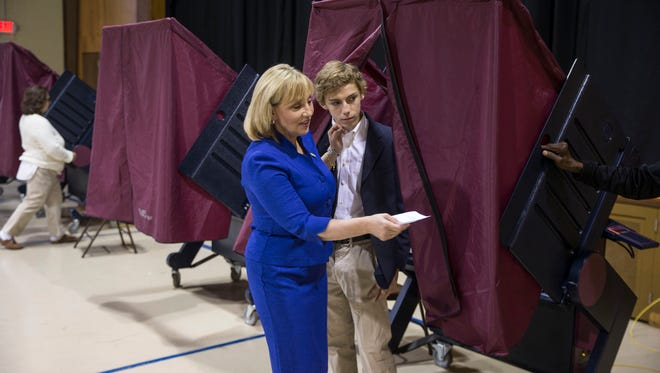 New Jersey Lt. Gov. Kim Guadagno casts her vote on election day at the Parish Center in Monmouth Beach. She emerges from the voting booth with her son Anderson. 