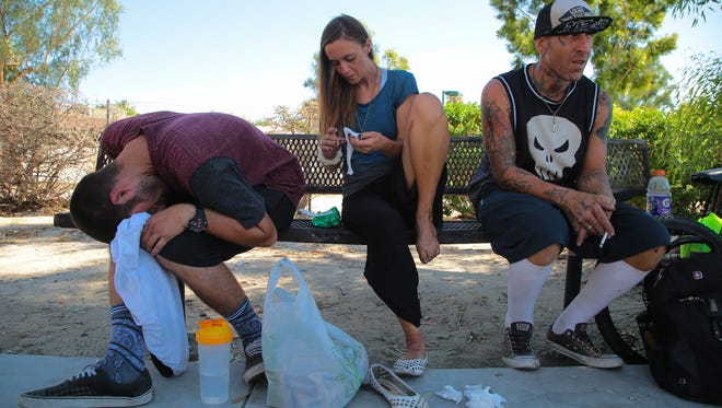 Blake Pricer, Shawna Maldin and Pete Gallagher sit on a bench outside of Baristo Park in Palm Springs, Calif., August 22, 2017.  Pricer is nodding off after using heroin while Shawna cleans off her feat.