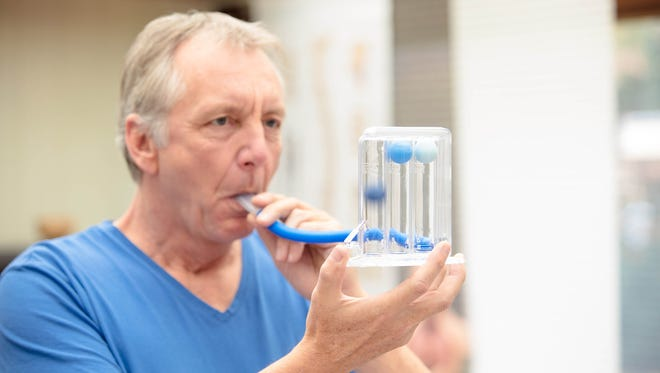 A male person, performing a simple lung function test by using a triflow. He has to blow into the tube, so the balls in the device lift a little bit according to the power of his breath.