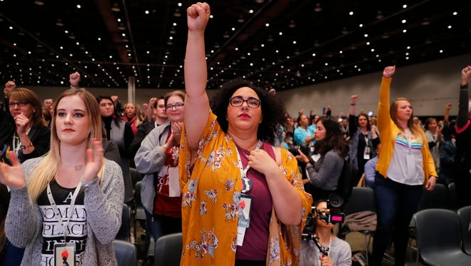 Women stand while listening to actress Rose McGowan speak at the inaugural Women's Convention held Oct. 27 in Detroit. McGowan recently went public with her allegation that film company co-founder Harvey Weinstein raped her.