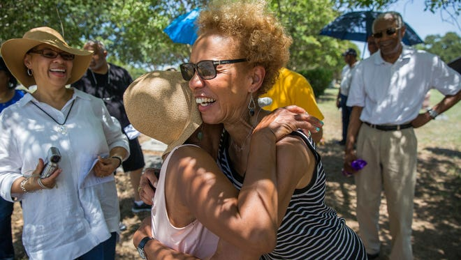 Bettye Kearse, center, hugs her fourth cousin Hattie Hester after a successful search for ancestors in Evergreen Cemetery in Austin, Texas.