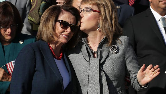 House Minority Leader Nancy Pelosi, D-Calif., gets a kiss from former Congresswoman and gun violence victim Gabby Giffords during a rally with fellow Democrats on the East Front steps of the U.S. House of Representatives October 4, 2017 in Washington, D.C. Pelosi will hold an event honoring Giffords Wednesday.