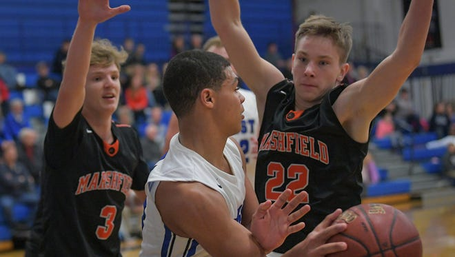 Karter Thomas (24) of Oshkosh West get double-teamed by Tommy Olson (3) and Cody Korth (22) of Marshfield. The Oshkosh West Wildcats hosted the Marshfield Tigers in a non-conference game Friday evening, November 24, 2017.