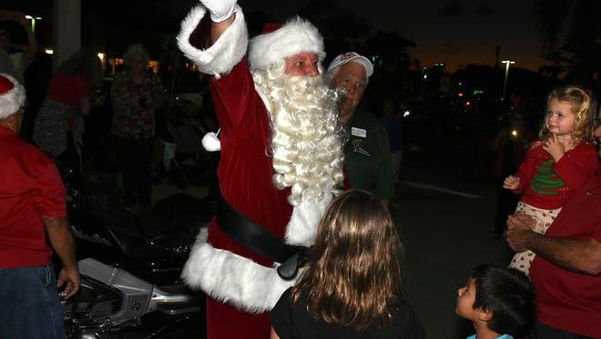 Santa greets his public, including Abigail Kuhn, 2. Santa and Mrs. Claus arrived Friday evening at the Shops of Marco, posing for pictures with children and officially kicking off the Christmas season.