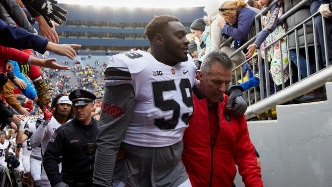 Ohio State coach Urban Meyer and offensive tackle Isaiah Prince head up the tunnel after Saturday's 31-20 victory at Michigan.