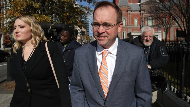 File photo shows federal budget director Mick Mulvaney (center), President  Trump's pick for acting director of the Consumer Financial Protection Bureau, returning to the White House after his first morning at work at the CFPB's headquarters in Washington, D.C.