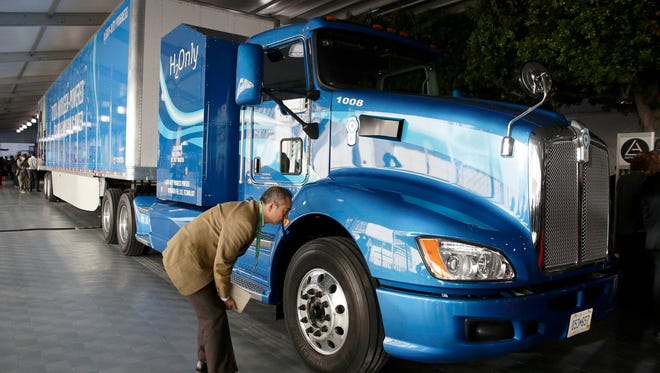 An attendee looks at Toyota's hydrogen fuel cell truck at the Los Angeles Auto Show, Thursday, Nov. 30, 2017, in Los Angeles.
