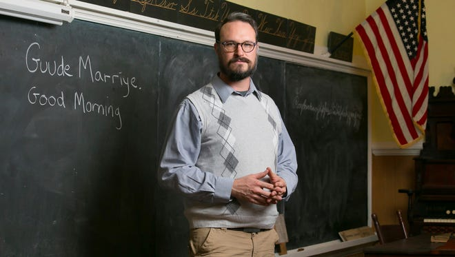 Patrick Donmoyer, building conservator and exhibit specialist, stands in the schoolroom  at the Pennsylvania German Cultural Heritage Center, at Kutztown University, in Kutztown, Pa., on Nov. 28, 2017.  Donmoyer, whose family moved to Lebanon County from Philadelphia in 1732, said that approximately 400,000 people speak Pennsylvania Dutch in the United States (principally in Pennsylvania, Ohio and Indiana) and Canada. Its influence is deepest in about 14 counties in the southeastern and central parts of Pennsylvania, with thousands of residents apart from Amish and several Mennonite communities.   (Jessica Griffin/The Philadelphia Inquirer via AP)