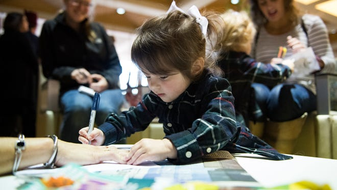 Laney Carroll, 2, draws a hand on a sheet of paper with high school football player autographs written on it at Shriners Hospitals for Children on Sunday, Dec. 10, 2017.
