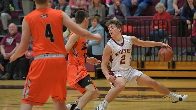 Austin Hecker (2) of Winneconne dribbles around Luke Rogers (12) of Ripon.  The Winneconne Wolves hosted the Ripon Tigers Tuesday evening in an East Central Conference matchup.