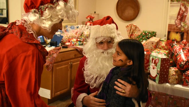 Santa and Mrs. Claus hear from Alina, 5. The non-profit Neighborhood Health Clinic hosted a holiday party for their patients and their children on Sunday at the clinic facility on Goodlette Rd.