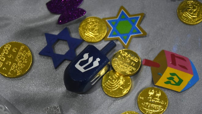 Dreidels, the Star of David, and the chocolate coins called Hanukkah gelt are symbols of the season.