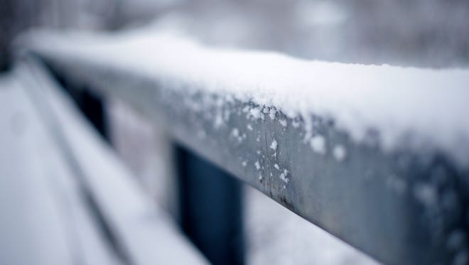 Snow covers a rail of a bridge on Prospect Avenue Monday, Dec. 18, 2017, in Wausau, Wis.