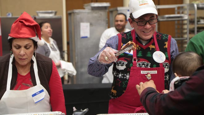 Mayor Robert Moon serves food to guests at the Well in the Desert Christmas event, December 25, 2017.
