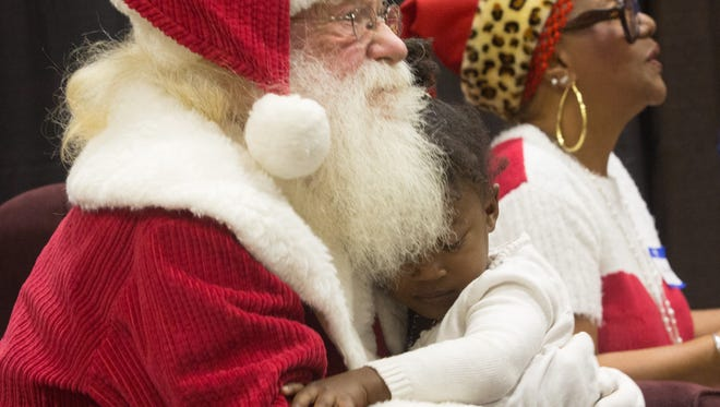 Jayla Rae Wash gets a hug from Santa at the Well in the Desert Christmas event, December 25, 2017. (Desert Sun file photo)