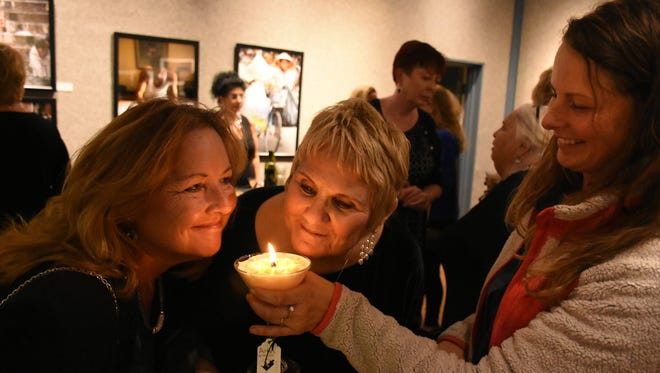 """Candlemaker Alexis Lessarde, right, offers a sniff of one of the martini candles she made and is selling at the gallery's giftshop. The Marco Island Center for the Arts held """"ARTini,"""" a drinks-themed fundraiser and party, Thursday evening at their gallery on Winterberry  Drive."""