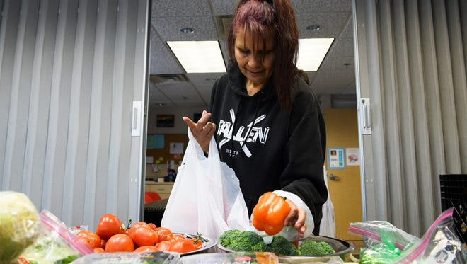Virginia Robinson picks up a bell pepper at the free farmer's market at the Greenville Free Medical Clinic on Thursday Jan. 25, 2018.
