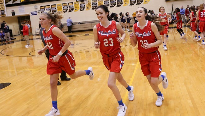 Kaiah Haberkorn (42), Sarah O'Day (23) and Maycee Woods (33) run off the floor happy following Plainfield's sectional semifinal win Friday night.