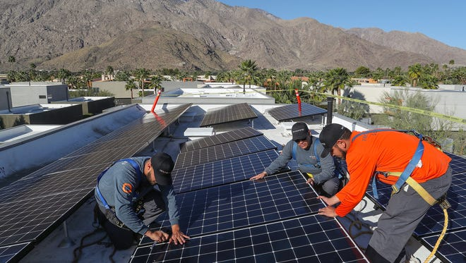 From left: Renova Solar technicians Luis Banuelos, Jeff Flores, and Genaro Munoz install solar panels on a Palm Springs home on Feb. 6, 2018.