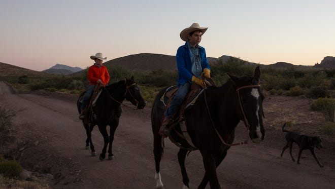 David and James Hurt ride their horses across the ranch as they make their way to round up cattle early one morning in the fall. The boys are active daily on the family ranch and both intend to continue the ranching tradition when they are older.