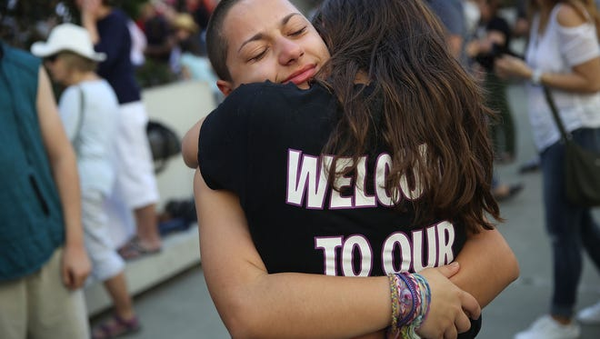 Emma Gonzalez is hugged as she joins other people after a school shooting that killed 17 to protest against guns on the steps of the Broward County Federal courthouse on Feb. 17, 2018 in Fort Lauderdale, Fla.