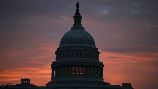 The sun lights up the sky behind the U.S. Capitol on Feb. 6, 2018, in Washington.